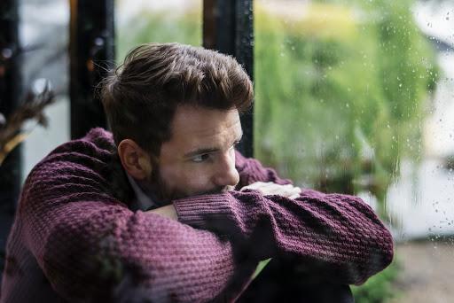 mężczyzna patrzący w okno