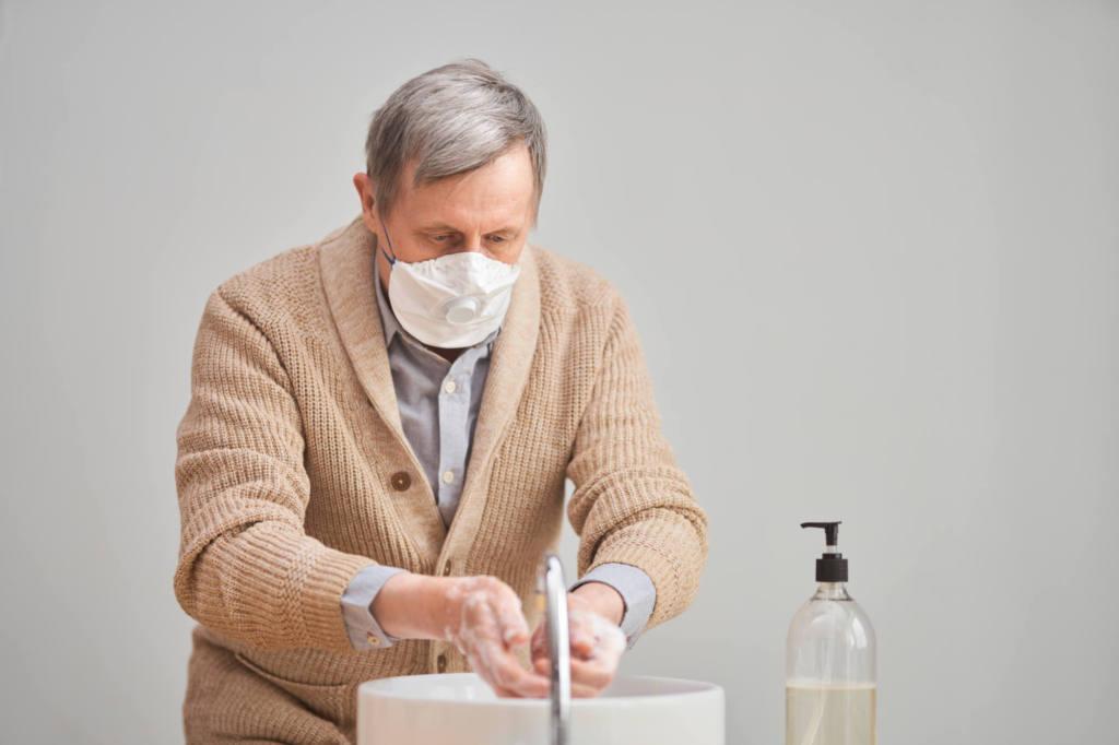 mężczyzna w maseczce myjący ręce